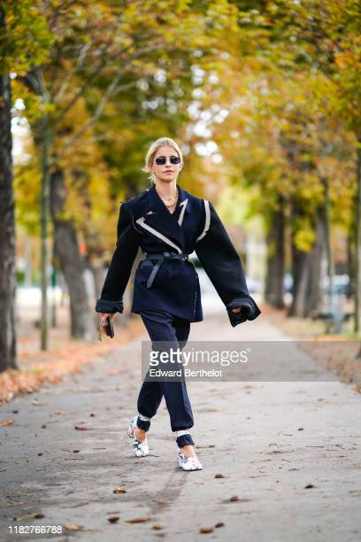 Caroline Daur wears sunglasses, necklaces, a navy blue oversized jacket with apparent seams and ripped hem white inserts, a black belt, a red mini...