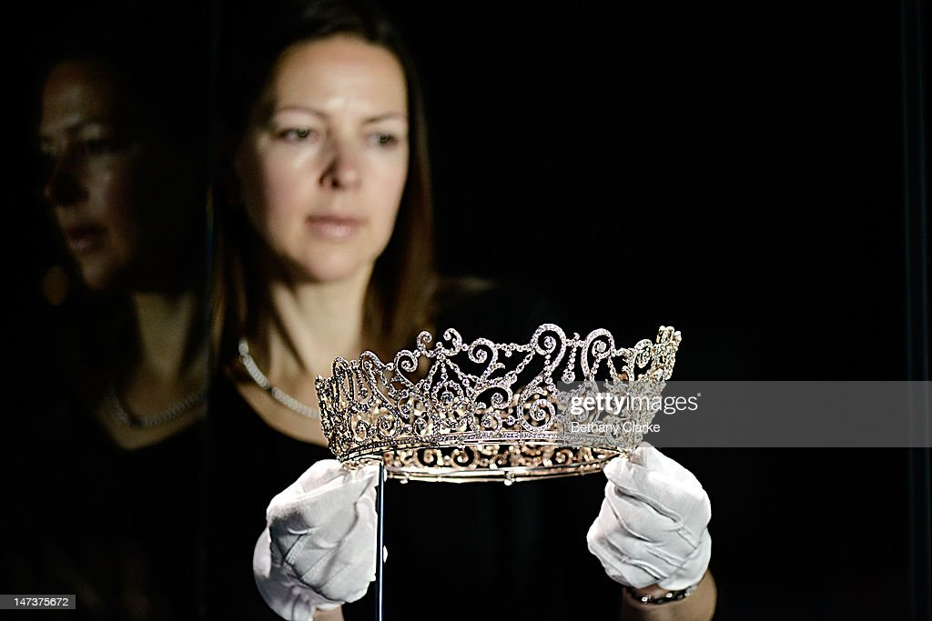 Caroline de Guitaut, Curator of Royal Collections, holds the Delhi Durbar Tiara, which was loaned to the Duchess of Cornwall in 2005, at the Diamonds: A Jubilee Celebration exhibition which forms part of the summer opening of Buckingham Palace on June 28, 2012 in London, England. 10,000 diamonds set in works acquired by six monarchs over three centuries go on display to mark Queen Elizabeth II's 60 year reign. With many items from the Queen's personal collection joining those chosen for their artistic significance and historical importance from the Royal Collection. The exhibition opens on Saturday and runs til 8th July and then again from July 31 to October 7.