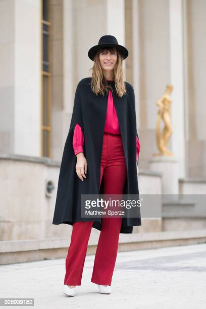 Caroline de Maigret is seen on the street attending Haider Ackermann during Paris Women's Fashion Week A/W 2018 wearing a black poncho with pink/red...