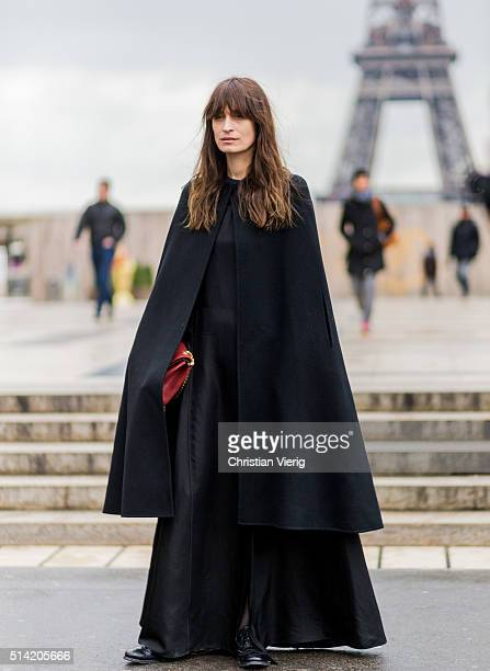 Caroline de Maigret wearing a long black cape and dress posing in front of the Eifel Tower outside Sacai during the Paris Fashion Week Womenswear...