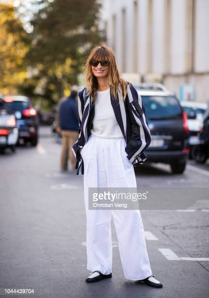 Caroline de Maigret wearing white wide leg pants striped jacket is seen outside Sacai during Paris Fashion Week Womenswear Spring/Summer 2019 on...