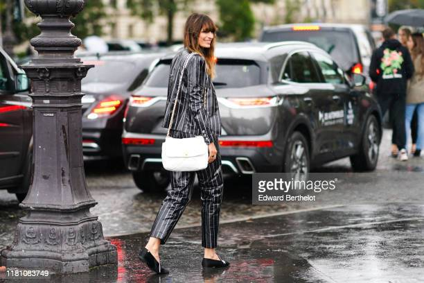 Caroline de Maigret wears a lustrous Chanel grey pantsuit with white stripes, a white Chanel bag, black Chanel rhinestone embellished flat shoes,...