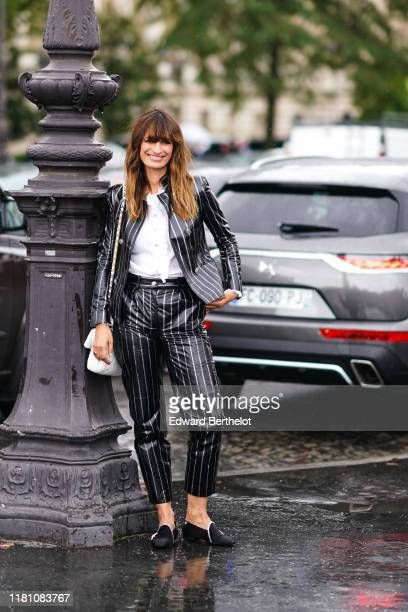 Caroline de Maigret wears a lustrous Chanel grey pantsuit with white stripes, a white frilly top, a white Chanel bag, black Chanel rhinestone...