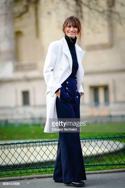 Caroline de Maigret wears a white coat flare pants with buttons a black turtleneck top outside Chanel during Paris Fashion Week Haute Couture...
