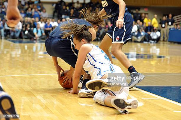 Caroline Doty of the Connecticut Huskies and Haley Peters of the Duke Blue Devils fight for a loose ball during the first half at Cameron Indoor...