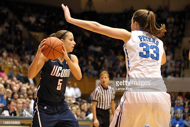 Caroline Doty of the Connecticut Huskies looks to pass against Haley Peters of the Duke Blue Devils at Cameron Indoor Stadium on January 30 2012 in...