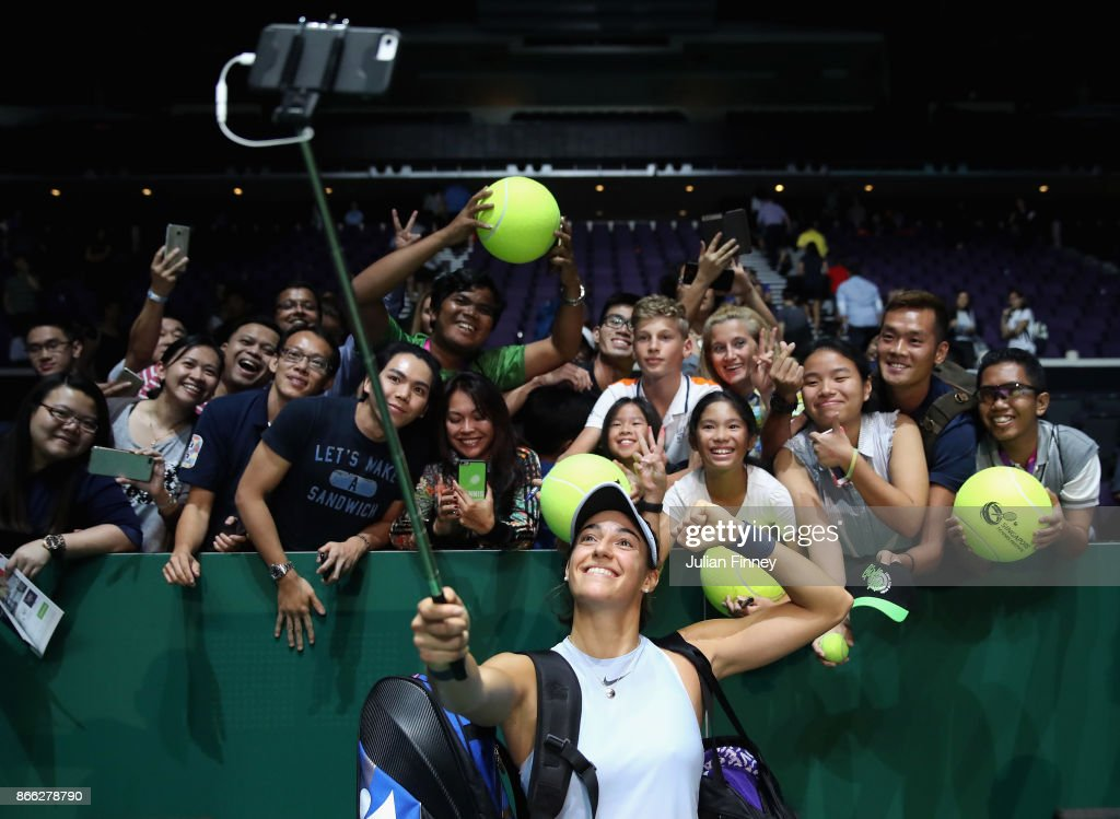 Caroline Garcia of France takes a selfie with fans as she celebrates victory in her singles match against Elina Svitolina of Ukraine during day 4 of the BNP Paribas WTA Finals Singapore presented by SC Global at Singapore Sports Hub on October 25, 2017 in Singapore.