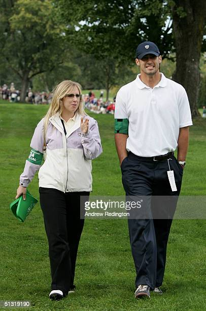 Caroline Harrington walks with Padraig's second cousin Joey Harrington of the Detroit Lions football team during the afternoon foursome matches at...