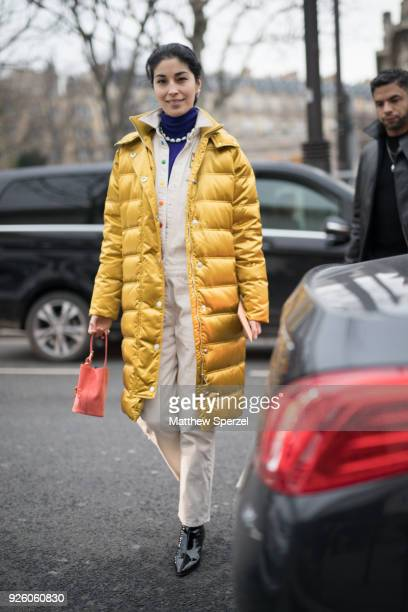 Caroline Issa is seen on the street attending Rick Owens during Paris Fashion Week Women's A/W 2018 Collection wearing a long yellow down coat with...