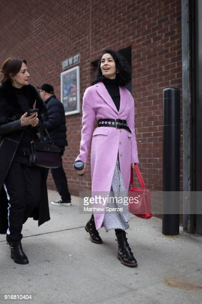 Caroline Issa is seen on the street attending SelfPortrait during New York Fashion Week wearing a pastel purple coat with black belt and red bag on...