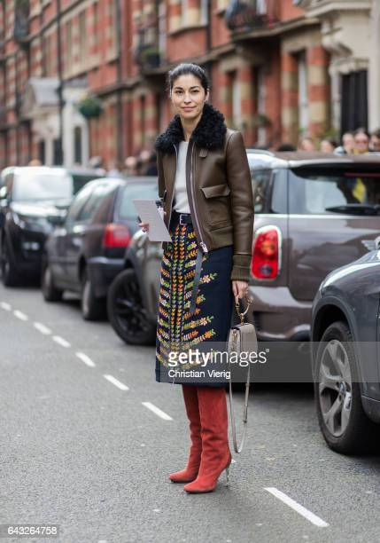 Caroline Issa wearing a brown leather jacket, a Chloe bag, red overknees, skirt outside Sharon Wauchob on day 4 of the London Fashion Week February...