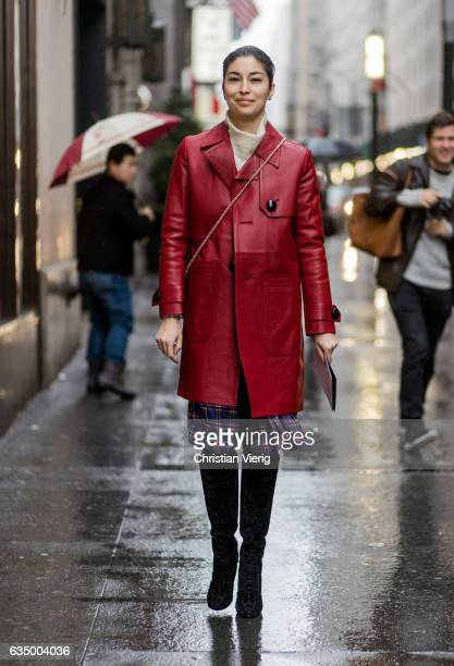 Caroline Issa wearing a red leather coat checked skirt overknees outside Victoria Beckham on February 12 2017 in New York City
