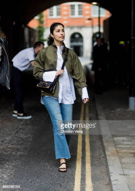 Caroline Issa wearing an olive jacket flared denim jeans sandals white button shirt during the London Fashion Week Men's June 2017 collections on...