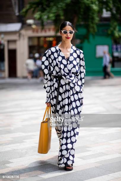 Caroline Issa wearing white navy dress with dots print is seen during London Fashion Week Men's June 2018 on June 9 2018 in London England