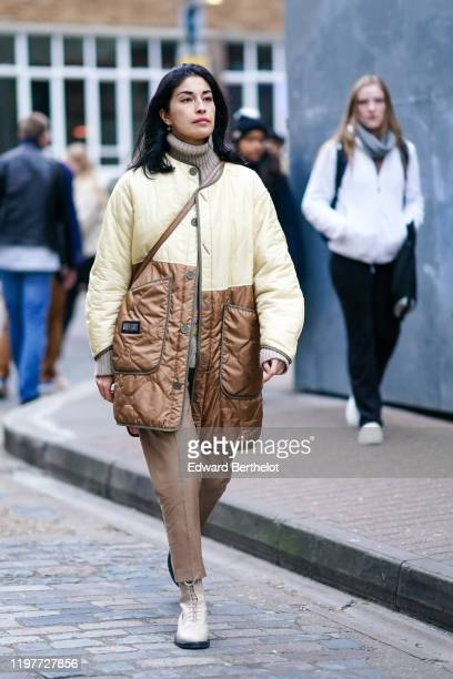 Caroline Issa wears a brown wool turtleneck pullover a yellow and brown lustrous long puffer coat pants shoes during London Fashion Week Men's...