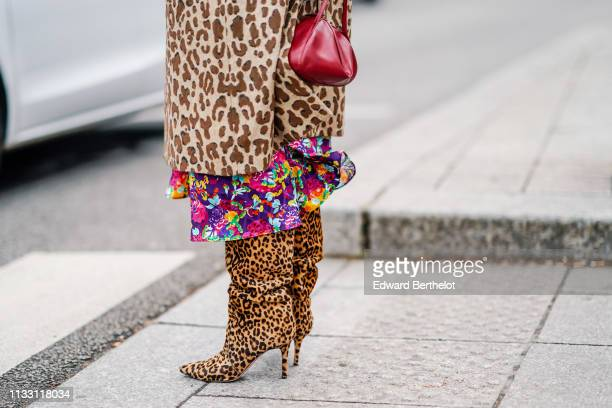 Caroline Issa wears a Dolce Gabbana brown leopard print coat a colorful floral print flowing dress a red handbag leopard print pointy high heeled...