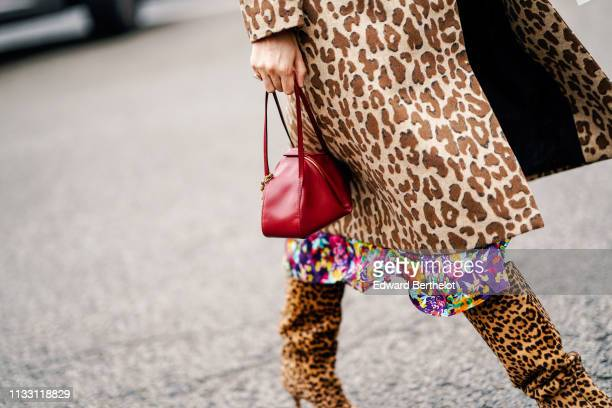 Caroline Issa wears a Dolce Gabbana brown leopard print coat, a colorful floral print flowing dress, a red handbag, leopard print pointy high heeled...
