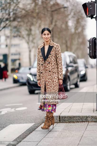 Caroline Issa wears a Dolce Gabbana brown leopard print coat with black lapels, a colorful floral print flowing dress, a red handbag, leopard print...