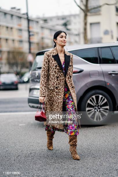 Caroline Issa wears a Dolce Gabbana brown leopard print coat with black lapels a colorful floral print flowing dress a red handbag leopard print...