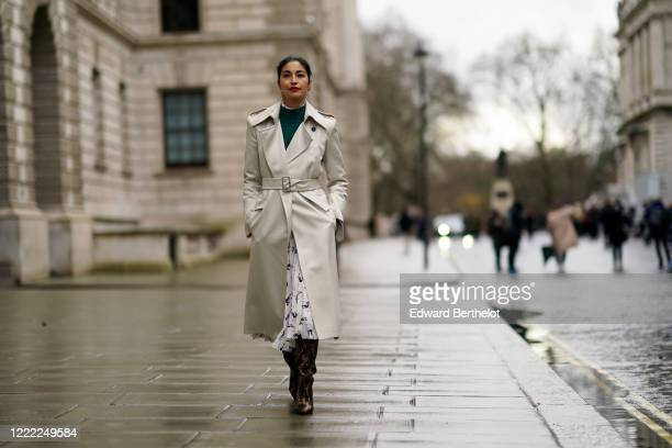 Caroline Issa wears a green pullover, a gray trench coat, a white pleated skirt, brown boots, during London Fashion Week Fall Winter 2020 on February...