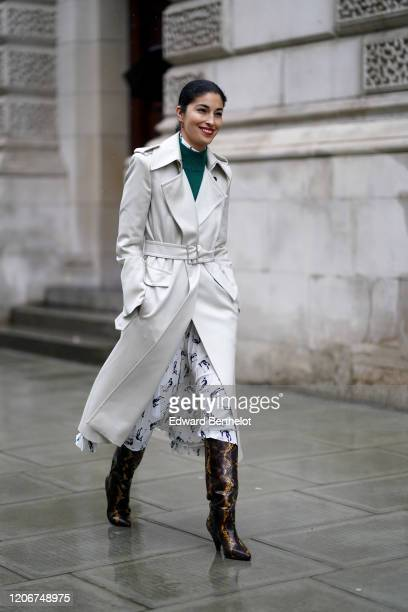 Caroline Issa wears a green pullover, a white long trench coat, a dress, black and brown pointy snake pattern printed boots, during London Fashion...