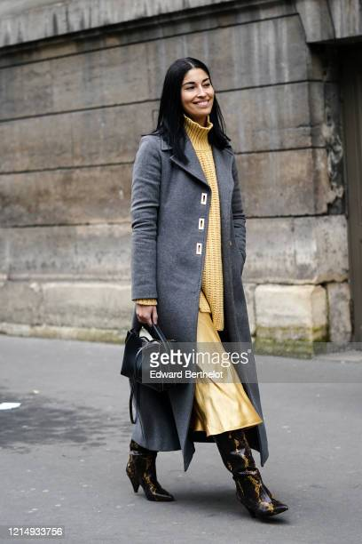Caroline Issa wears a yellow wool turtleneck woven pullover, a gray long coat, a black leather bag, a yellow lustrous silky skirt, black and yellow...