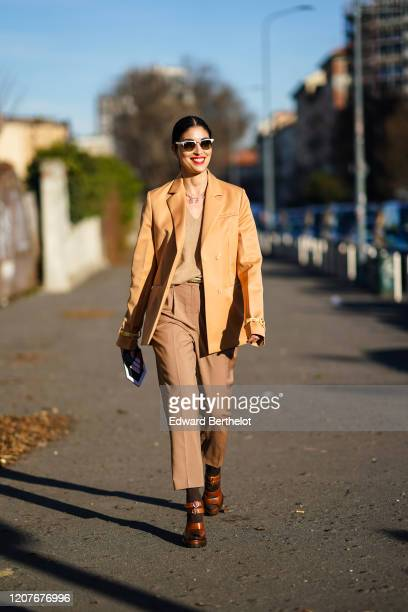 Caroline Issa wears sunglasses, a pale brown leather jacket, a beige top, pants, shoes, outside Prada, during Milan Fashion Week Fall/Winter...