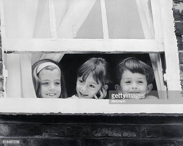 Caroline Kennedy and her cousins Tina and Anthony Radziwill play peekaboo with newsmen gathered before the Radziwill residence here Mrs Jacqueline...