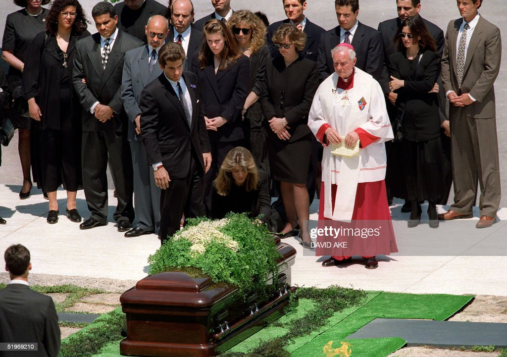 Caroline Kennedy Schlossberg kneels 23 May 1994 at Arlington Cemetery in Washington, D.C. at the foot of her mother's casket as her brother John Kennedy Jr (L) looks on during grave side ceremonies for former US First Lady Jacqueline Kennedy-Onassis. Onassis was buried next to her first husband US President John F. Kennedy.