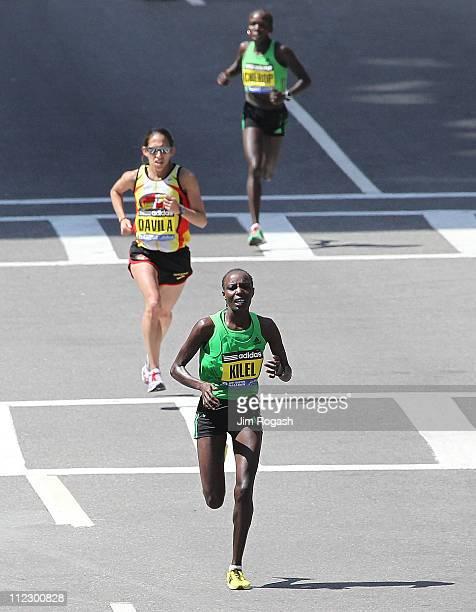 Caroline Kilel of Kenya runs ahead of Desiree Davila of the United States to win the women's division of the 115th running of the Boston Marathon on...