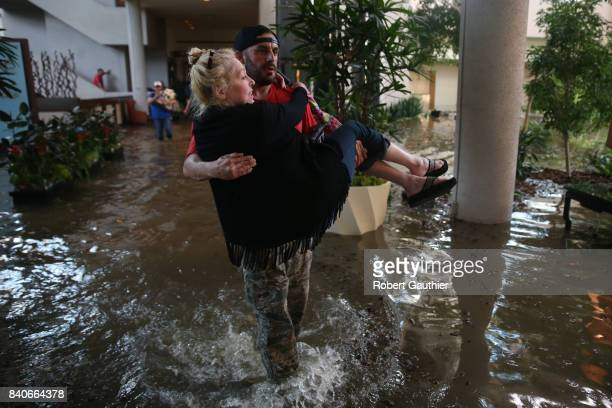 CaroLine Kirkpatrick of Salt Lake City Utah is carried through the lobby of the Omni Hotel by rescue worker Adam Caballero as the last of hundreds to...