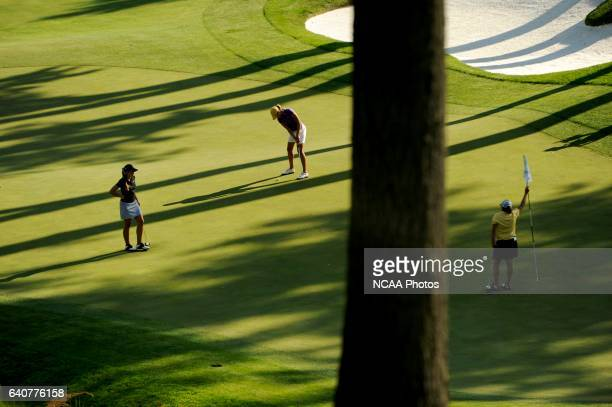Caroline Martens of Louisiana State University prepares to putt while Kathleen Ekey of the University of Alabama looks on and Maria Hernandez of...