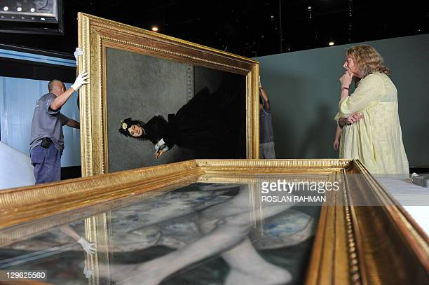 Caroline Mathieu exhibition curator from the Musee d'Orsay in Paris checks the newly shipped painting entitled 'La dame gant 1869' by French painter...