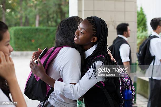 Caroline Mogomela hugs Yesenia Villada on her first day of school at St Patrick Secondary School in Toronto September 2 2014 Mogomela came from...