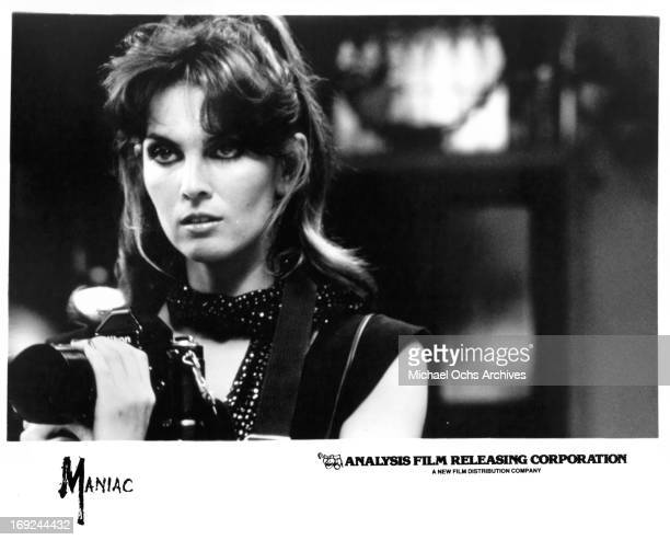 Caroline Munro holds a camera in a scene from the film 'Maniac' 1980