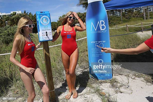Caroline Oliveira and Rachel Scherdin help unveil one of 50 sunscreen dispensers that are being setup along the beach on March 13 2015 in Miami Beach...