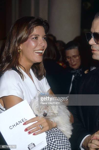 Caroline Princess of Monaco holding her pet dog talks with German fashion designer Karl Lagerfeld at the AutumnWinter 19881989 fashion show in Paris...