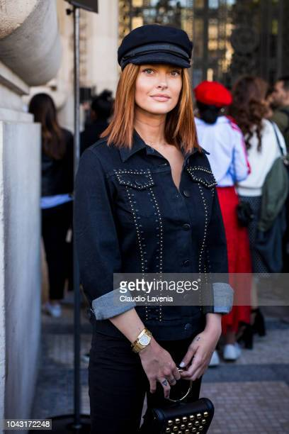 Caroline Receveur wearing a blue denim shirt and a black baker boy hat is seen after the Elie Saab show on September 29 2018 in Paris France