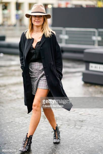 Caroline Receveur wears a hat a balck jacket a black top a gray skirt shoes and attends Le Defile L'Oreal Paris as part of Paris Fashion Week...