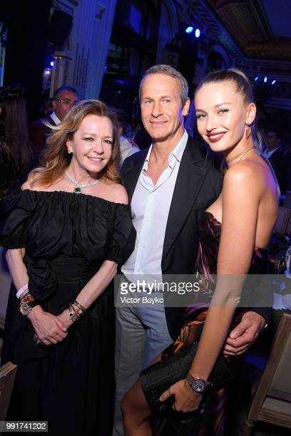 Caroline Scheufele poses for a picture with Chopard auction winner Kristina Romanova and Vladislav Doronin during amfAR Paris Dinner 2018 at The...