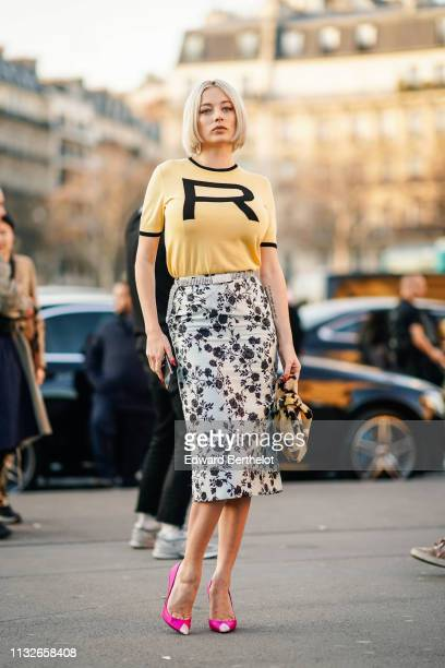"""Caroline Vreeland wears a yellow """"R"""" Rochas t-shirt, a white and black floral print skirt, a tiger print bag, pink pointy high heel pumps shoes,..."""