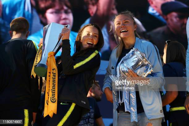 Caroline Weir and Claire Emslie of Manchester City Women hold the FA Women's Continental Cup and the SSE Women's FA Cup trophy on stage during the...