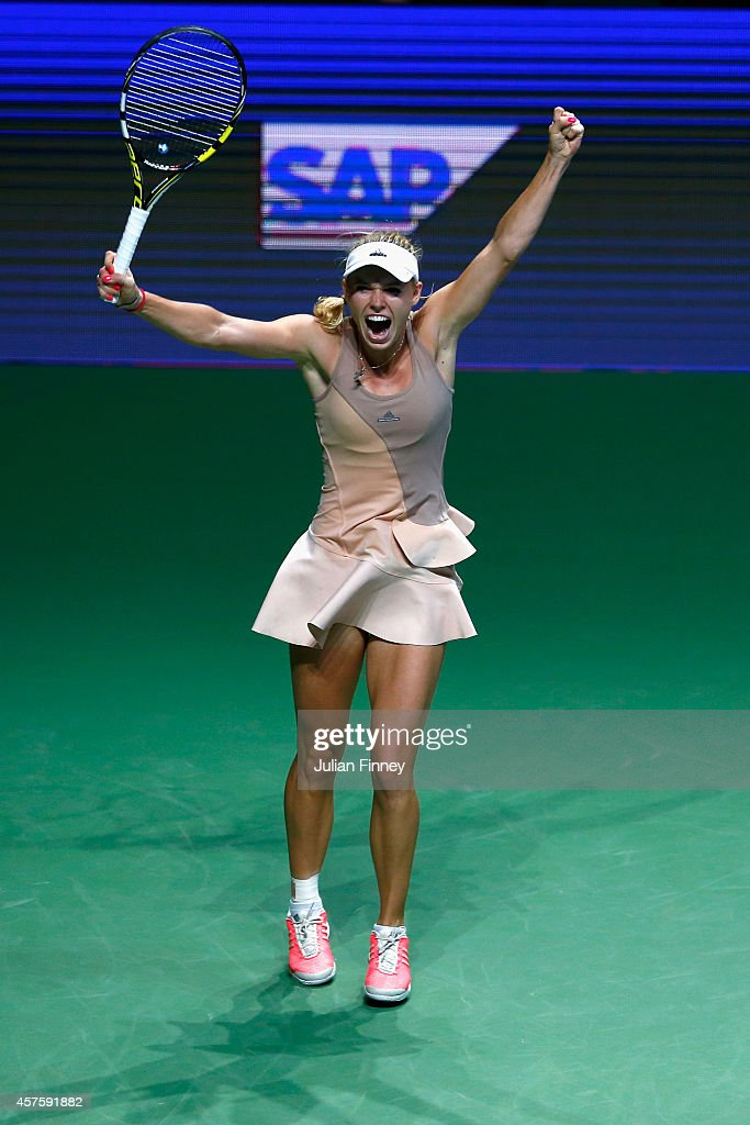 Caroline Wozniacki of Denmark celebrates defeating Maria Sharapova of Russia during day two of the BNP Paribas WTA Finals tennis at the Singapore Sports Hub on October 21, 2014 in Singapore.
