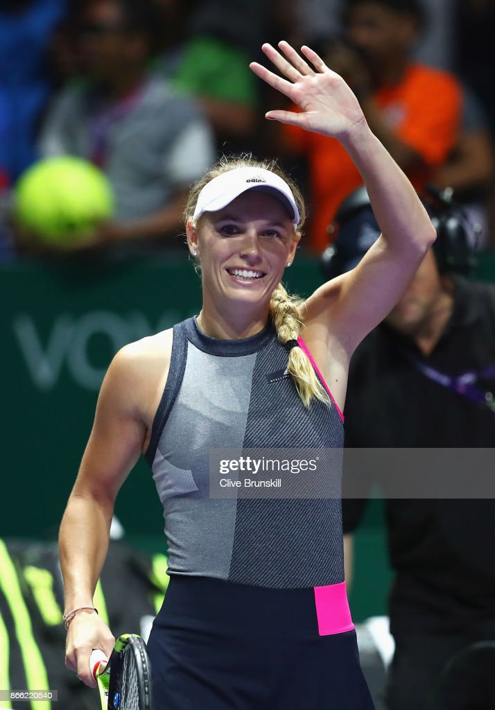Caroline Wozniacki of Denmark celebrates victory in her singles match against Simona Halep of Romania during day 4 of the BNP Paribas WTA Finals Singapore presented by SC Global at Singapore Sports Hub on October 25, 2017 in Singapore.