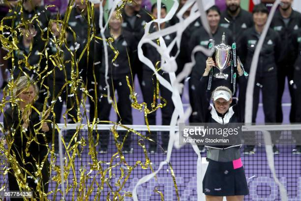 Caroline Wozniacki of Denmark celebrates victory with the Billie Jean King trophy in the Singles Final against Venus Williams of the United States...