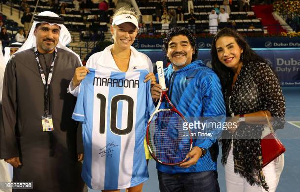 Caroline Wozniacki of Denmark exchanges gifts with football legend Diego Maradona as they pose for a picture with Salah Tahlak, Tournament Director...