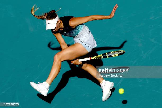 Caroline Wozniacki of Denmark hits a ball between her legs while playing Monica Niculescu of Romania during the Miami Open Presented by Itau at Hard...