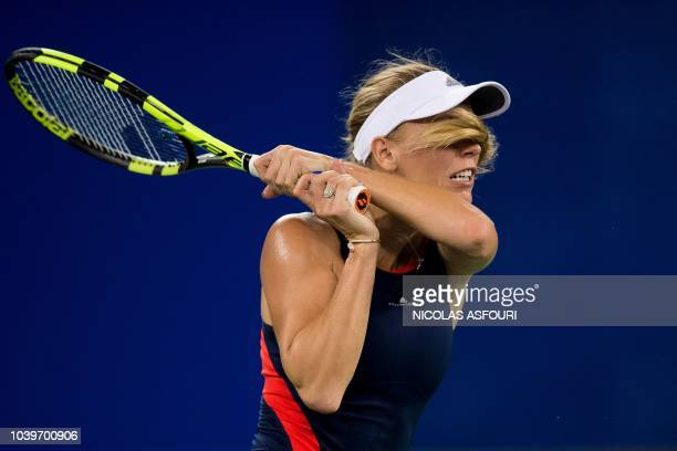 Caroline Wozniacki of Denmark hits a return against Rebecca Peterson of Sweden during their women's singles third round match of the WTA Wuhan Open...
