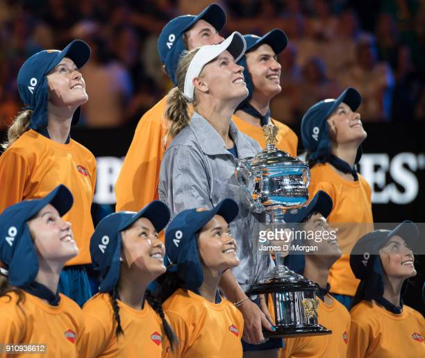 Caroline Wozniacki of Denmark holding the Daphne Akhurst Memorial Cup with ball kids after winning the women's singles tournament on day 13 of the...