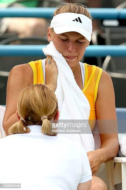 Caroline Wozniacki of Denmark is treated by WTA trainer Kerri Whitehead before retiring from her match against Maria Kirilenko of Russia during the...